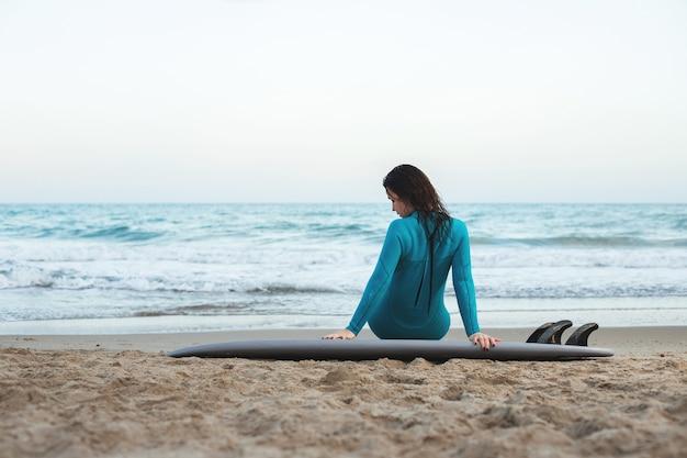 Fille de surfeur marchant avec planche sur la plage de sable. surfeuse femme. belle jeune femme à la plage.