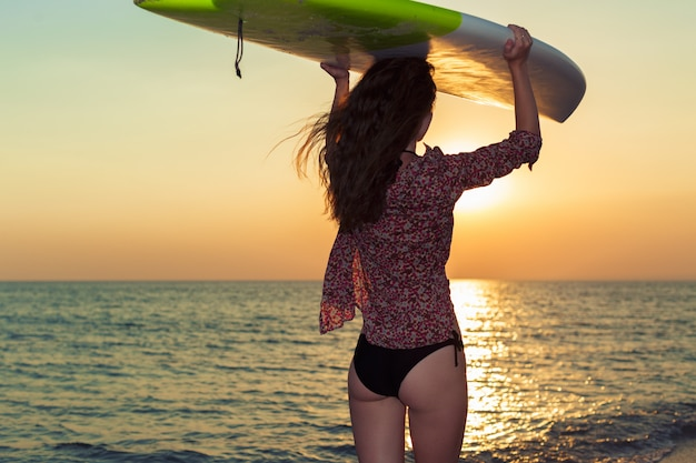 Fille surfeur, surf, regarder, plage océan, coucher soleil