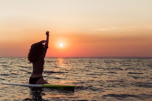 Fille de surfeur surfant en regardant le coucher de soleil sur la plage de l'océan