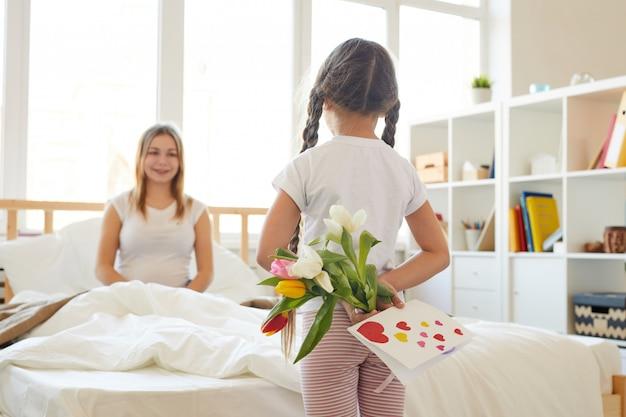 Fille surprenant maman avec des fleurs