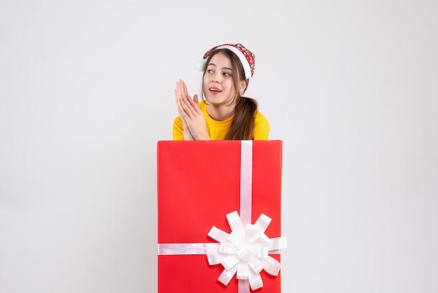 Fille surprise avec bonnet de noel debout derrière un grand cadeau de noël sur blanc