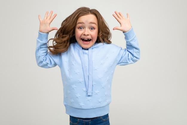 Fille surprise dans un sweat à capuche bleu sourit joyeusement tout en tenant ses mains devant la caméra sur un mur gris clair