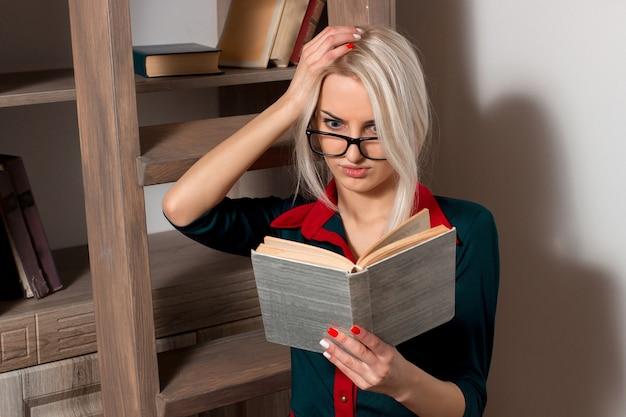 Fille surprise dans des verres et dans une robe bleue tenant un livre ouvert dans ses mains