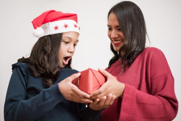Fille surprise et excitée avec un chapeau de noël recevant un cadeau de sa mère.