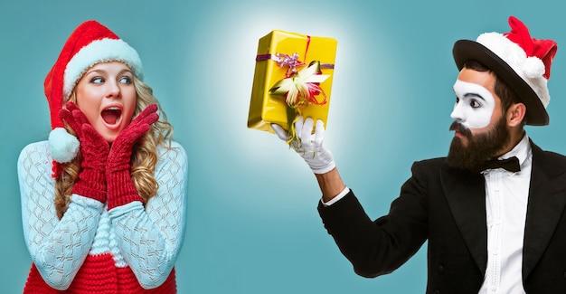La fille surprise et heureuse habillée en bonnet de noel et mime. concept de vacances avec fond bleu.