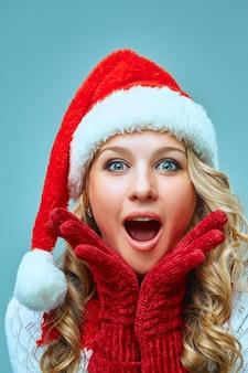 La fille surprise et heureuse vêtue d'un bonnet de noel. concept de vacances avec fond bleu.
