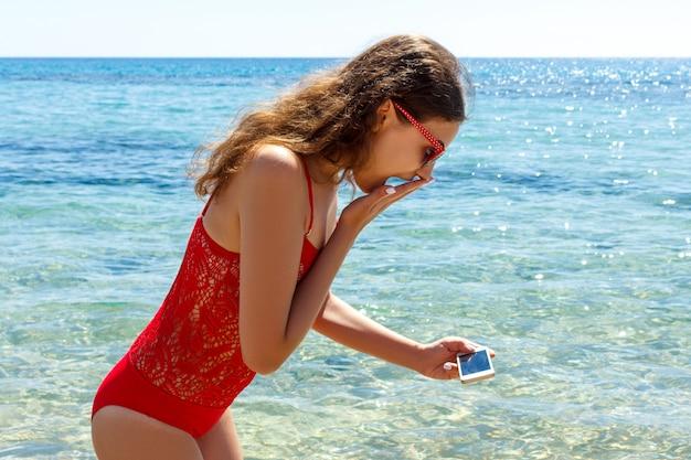 Une fille surprise et heureuse a vu quelque chose dans la mer