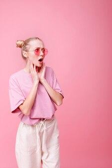 Fille surprise à lunettes sur rose