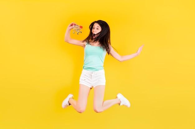 Fille surprise avec panier sautant sur un mur jaune