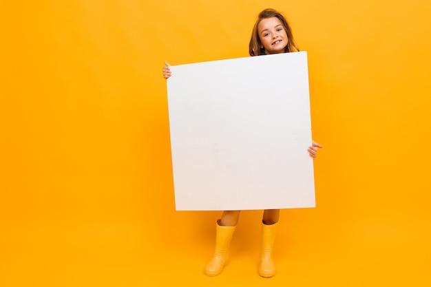 Fille surprise tenant un panneau d'affichage sur jaune avec espace copie