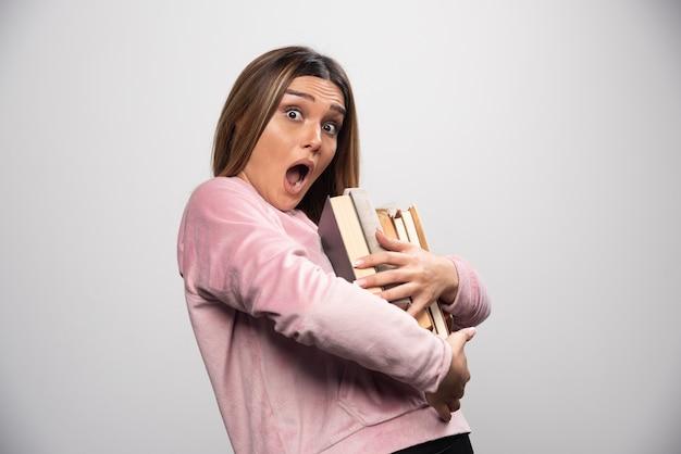 Fille en swaetshirt rose tenant et portant une lourde pile de livres.