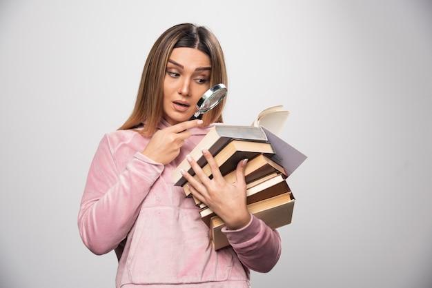 Fille en swaetshirt rose tenant un stock de livres et essayant de lire celui du haut avec une loupe.