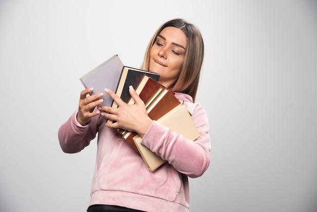 Fille en swaetshirt rose tenant et transportant une lourde pile de livres