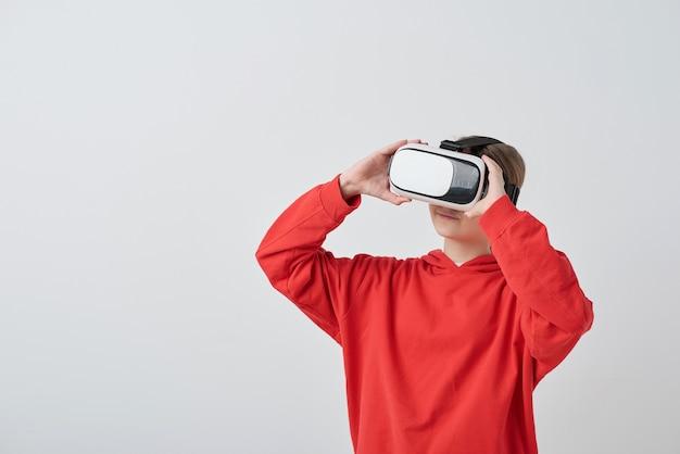 Fille en sweat à capuche rouge à l'aide de lunettes de réalité virtuelle tout en regardant un film en 3d
