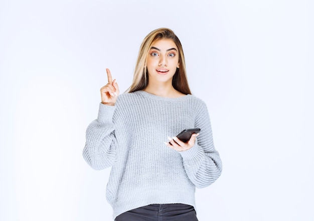 Fille en sweat-shirt gris tenant un smartphone noir et a une bonne idée.