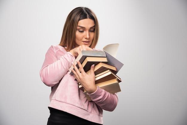 Fille en sweat-shirt rose tenant un stock de livres et essayant de lire celui du haut avec une loupe.
