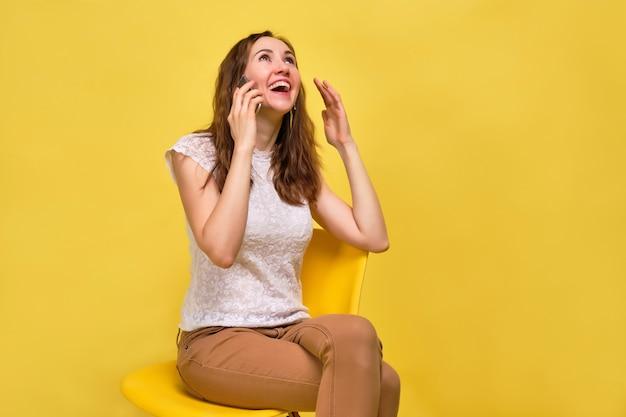 Une fille en t-shirt blanc et jean marron sur fond jaune parle joyeusement sur le smartphone.