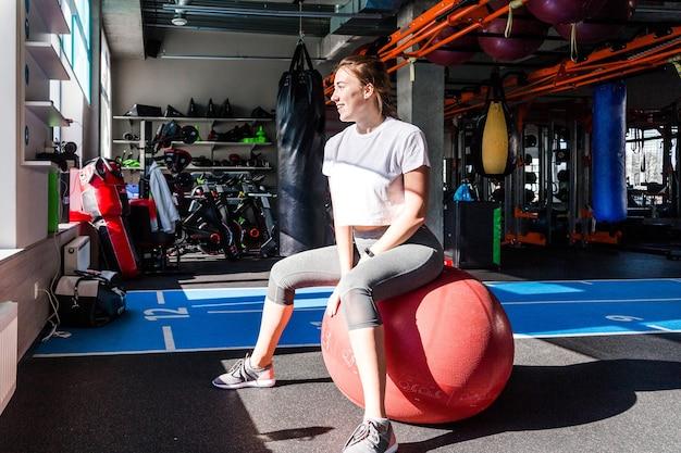 Une fille en t-shirt blanc et leggings gris est assise sur un ballon de fitness dans un club de fitness. lumière du soleil et ombres dures dans un club de fitness