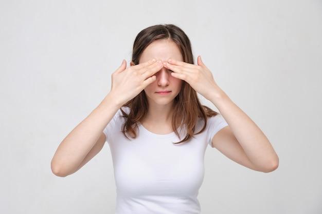 Une fille en t-shirt blanc masse ses paupières. le concept de douleur intense devant la tête.