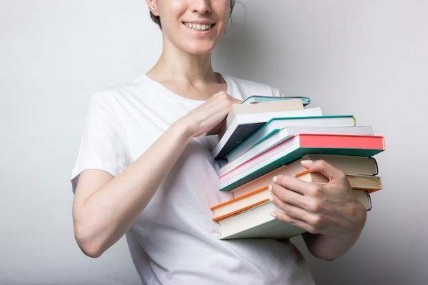 Une fille en t-shirt blanc tient beaucoup de livres dans ses mains. éducation, manuels de formation