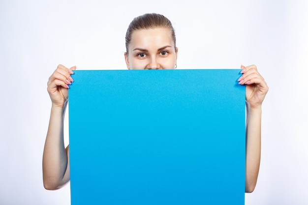 Une fille en t-shirt blanc tient dans ses mains une grande banderole vierge bleue.