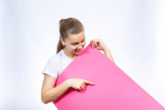 Une fille en t-shirt blanc tient dans ses mains une grande banderole vierge rose.
