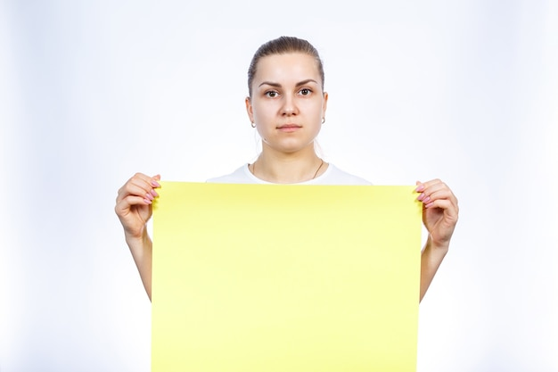 Une fille en t-shirt blanc tient une grande banderole vierge jaune.