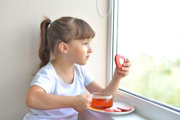 Une fille en t-shirt blanc tient une tasse de thé et un foie en forme de cœur rouge debout près de la fenêtre, regardant. délicieuse collation sucrée. en sécurité à la maison, auto-isolement pendant une pandémie.