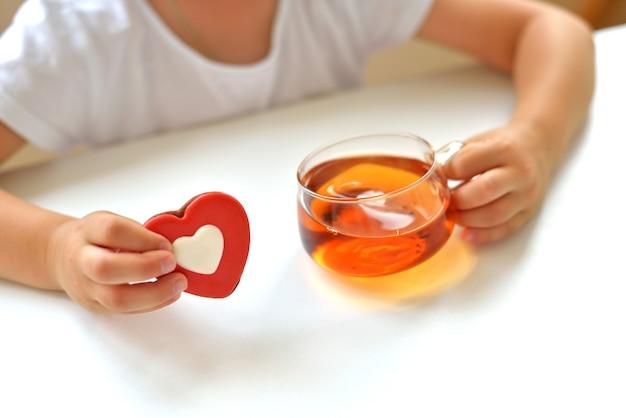 Une fille en t-shirt blanc tient une tasse de thé et un foie en forme de cœur rouge. délicieux concept de collation sucrée.