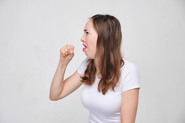 La fille en t-shirt blanc tousse fortement. concept de rhume ou de grippe.
