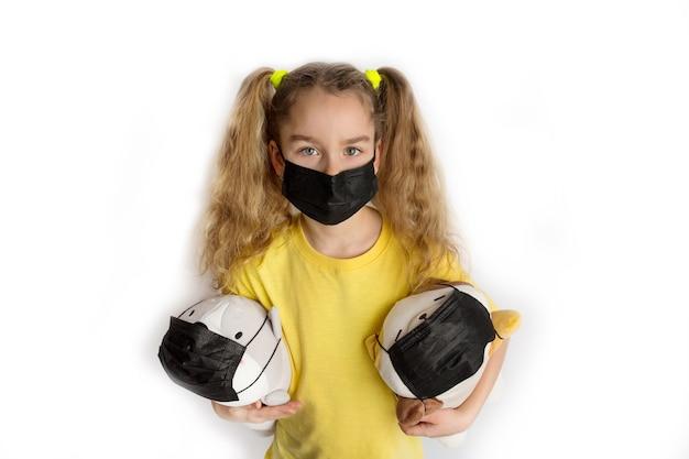 Fille en t-shirt jaune et masque noir covid19 sur fond blanc avec des jouets dans un masque. photo de haute qualité
