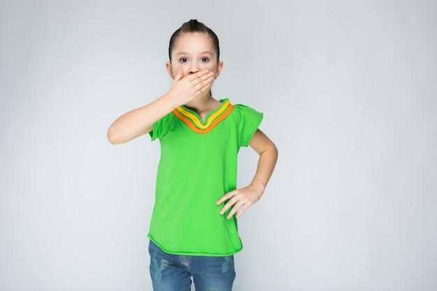 Fille en t-shirt vert et jean bleu sur gris.