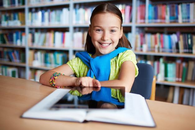 Fille avec tablette numérique dans la bibliothèque