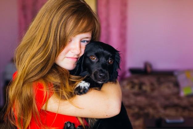Fille avec des taches de rousseur sur son visage tenant un chien noir dans ses bras et câlins