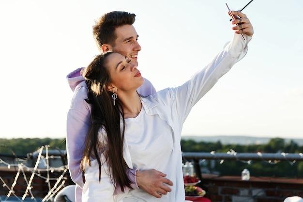 Fille takea un selfie avec son petit ami debout sur le toit