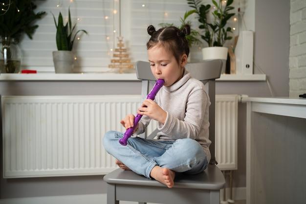 Une fille talentueuse joue de la flûte. apprendre en ligne à jouer des instruments de musique.