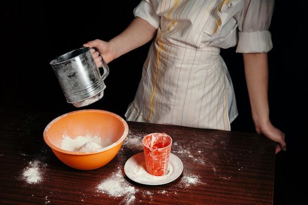 La fille tamise la farine dans un tamis en acier