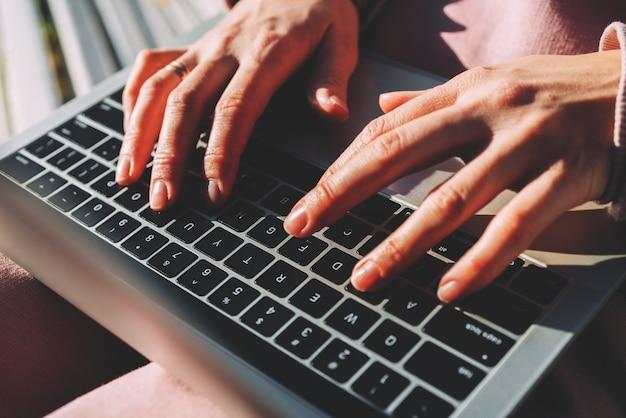 La fille tape le texte derrière un ordinateur portable alors qu'elle est assise sur un banc dans un parc en automne.