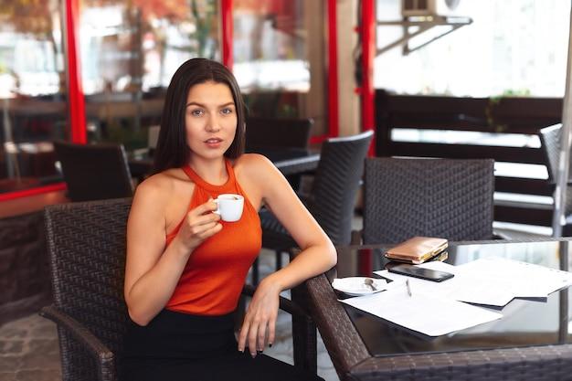 Fille avec une tasse de café assis dans un café. grand sourire. belle peau propre. femme d'affaires après avoir signé des documents. réunion d'affaires.