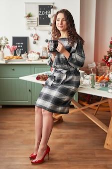 Fille avec une tasse dans la cuisine du nouvel an