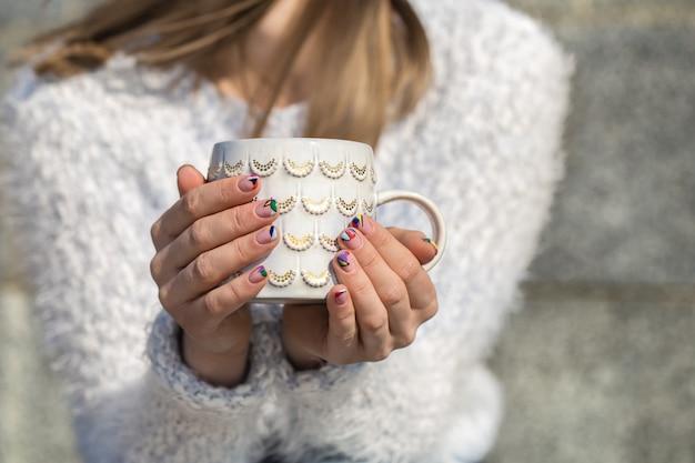 Fille avec une tasse dans les mains