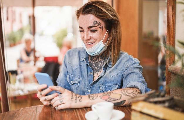 Fille avec tatouage à l'aide de téléphone portable tout en portant un masque de protection du visage assis à la cafétéria