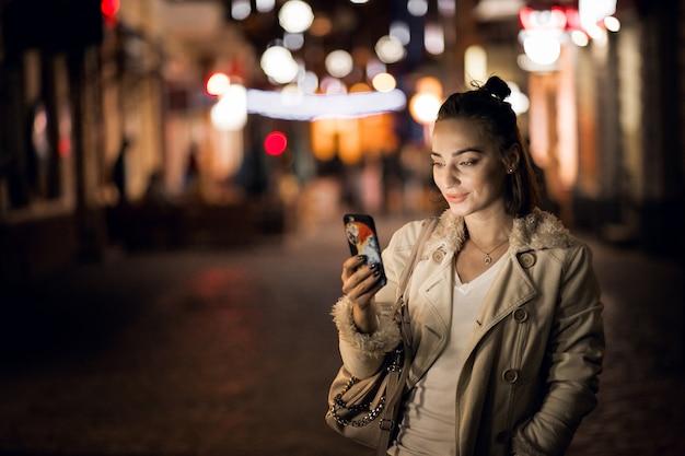 Fille avec téléphone la nuit