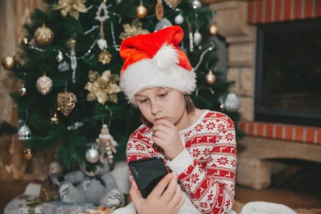 Fille avec téléphone portable à l'arbre de noël dans le salon