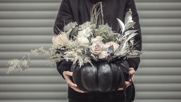 Fille tenant un arrangement floral dans une citrouille