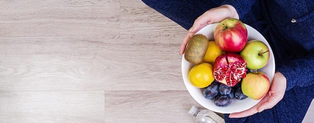 Fille tenant une assiette blanche avec des pommes, des prunes, des kiwis et des grenades. alimentation équilibrée. concept de remise en forme et de mode de vie sain. bannière. vue de dessus