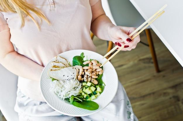 Fille tenant des baguettes, bol de bouddha avec des nouilles de verre, haricots, poitrine de poulet, épinards, roquette et concombre