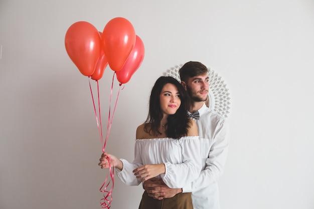 Fille tenant des ballons en forme de coeur, tandis que son petit ami lui tient