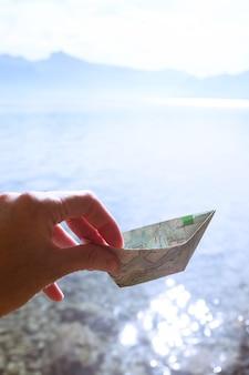 Fille tenant un bateau en papier à partir d'une carte sur fond de lac, été et voyage