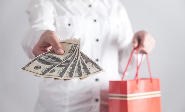 Fille tenant des billets en dollars avec un sac à provisions. achats